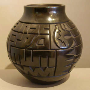 Bear with heart line and geometric design carved into a polished black jar