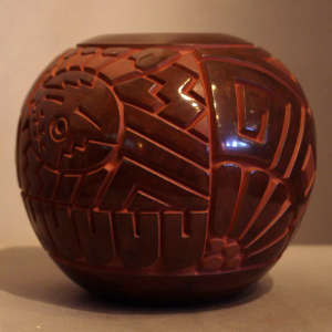 Katsina face and geometric design carved into a brown jar