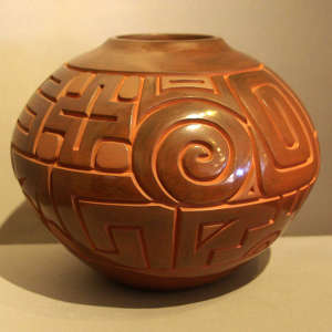 Cross, Tularosa spiral and geometric design carved into a polished brown jar