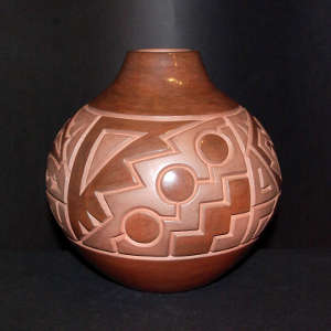 Carved stylized bear and geometric design on a brown on brown jar