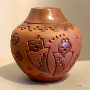 Geometric design and yei figures carved into a red jar