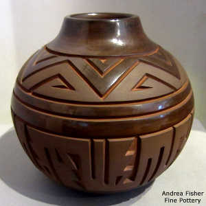 Geometric design carved into a brown on brown jar