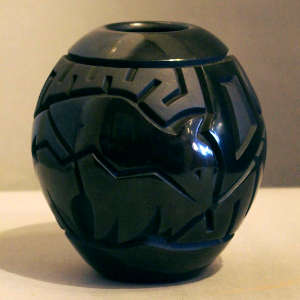 Buffalo, storm cloud and geometric design carved into a black jar
