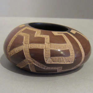 Sgraffito geometric design on a small brown bowl