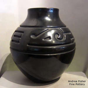 An avanyu and geometric design carved into a black jar