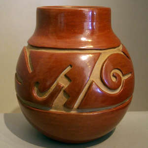 Geometric design carved into a deep red jar