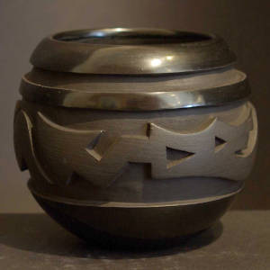 Avanyu design carved in to a black on black jar