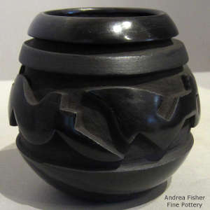 An avanyu design carved into a black on black jar