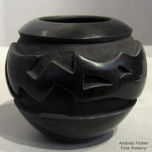 An avanyu design carved into a black jar