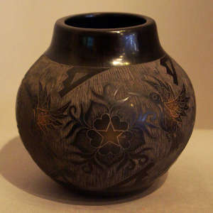 Sgraffito hummingbirds, flowers and geometric designs on a black jar