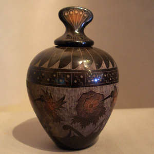 Sgraffito hummingbird, floral and geometric design on a lidded black jar