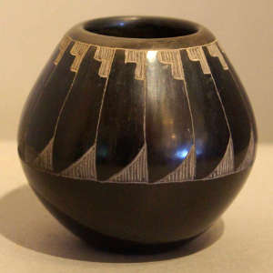 Sgraffito feather design on a black jar