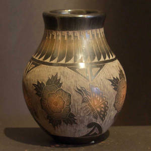 Sgraffito flower, butterfly and feather design on a black jar with sienna spots