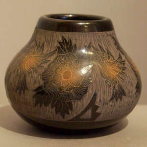 Sgraffito hummingbird and floral motif on a black jar with sienna spots