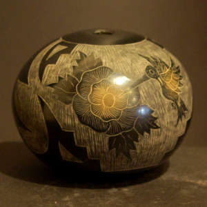 Sgraffito hummingbird and flower design on a black jar with sienna spots