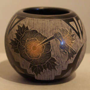 Sgraffito floral, hummingbird and geometric design on a black jar with sienna spots