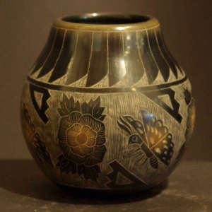 Sgraffito butterfly, flower and geometric design on a black jar with sienna spots