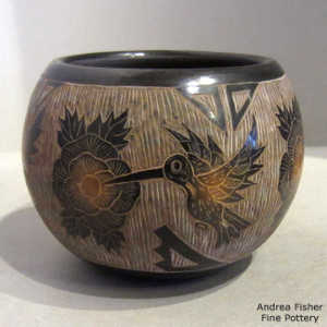 Sgraffito hummingbird, flower and geometric design on a black jar with sienna spots