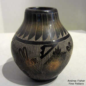 Sgraffito flower, dragonfly, feather and geometric design on a black jar with sienna spots