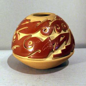 Double avanyu design carved into a red and tan jar