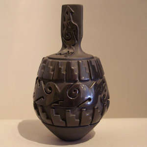 Avanyu and kiva step step design carved into a lidded black jar plus avanyu carved into lid