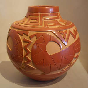 Bird and geometric design carved into a polished red jar