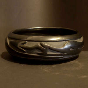 An avanyu design carved into a black bowl