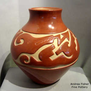 An avanyu design carved into a red jar