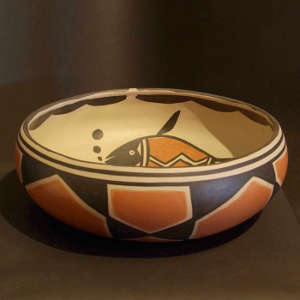 A fish and geometric design inside, geometric design outside on a polychrome bowl