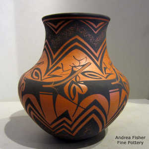 Deer, heart line and geometric design on a red and black jar
