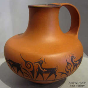 Deer, heart line and geometric designs on an orange water pitcher