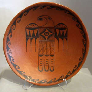 Red and black thunderbird and water designs on a redware bowl