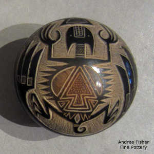 Sgraffito feather, horned toad and geometric design on a black seed pot with sienna spots