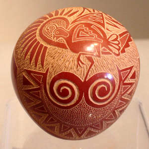 Sgraffito and painted quail, sun face and geometric design on a red seed pot